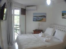 Quarto com cama QueenSize, tv , ar condicionado split, armário aberto.