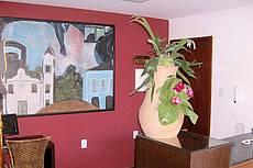 Foto de nossa recepção, onde aparece ao fundo, um dos vários quadros do pintor Flavio Gadelha, que ilustram nossas paredes.