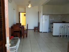 Sala e cozinha americana do apartamento térreo vista para o mar