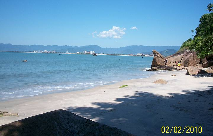 Ao fundo a cidade de Caraguá. Praia de mar calmo e estreita. Acesso por trilhas.