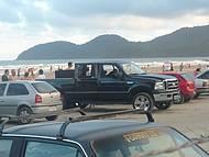 Uma bela praia. Carros estacionados na areia..