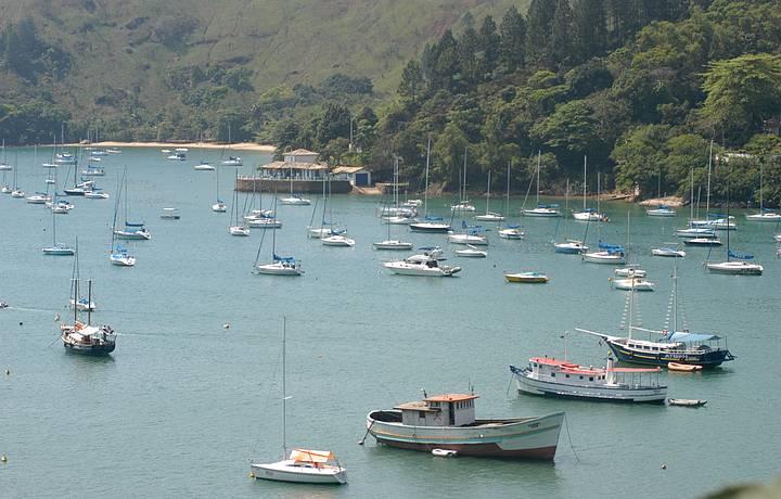Porto natural abriga barquinhos de pesca e muitas lanchas
