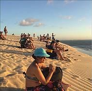 Todos sentam na duna para ver o por do sol