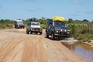 Veículos encaram estradas precárias de terra e barro