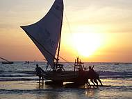 Pescadores levam suas jangadas para o mar  ao raiar do sol