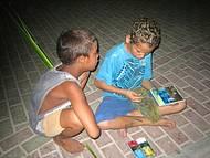 Crianças produzem os artesanatos na frente dos turistas.