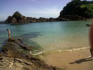 Maravilhosa praia de águas calmas e translucidas em um ambiente bucólico.